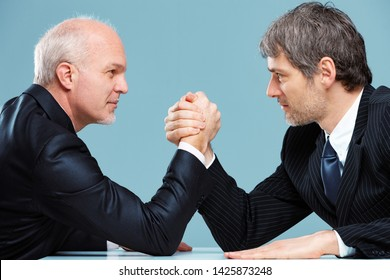 Two businessmen facing off against each other in a challenge for supremacy arm wrestling over an office table with looks of determination in a close up side view