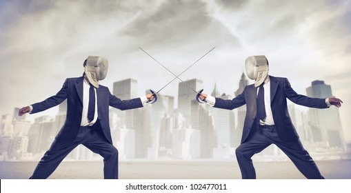 Two businessmen fencing with cityscape in the background