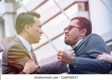 Two businessmen are fighting as enemy. They are very angry in the public