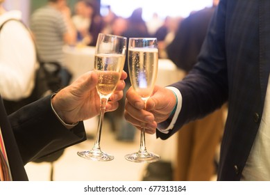 Two businessmen with glasses of champagne at a grand meeting