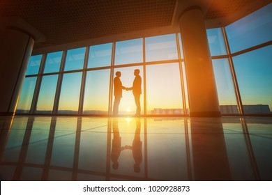 The two businessmen handshake in the office on the bright sun background