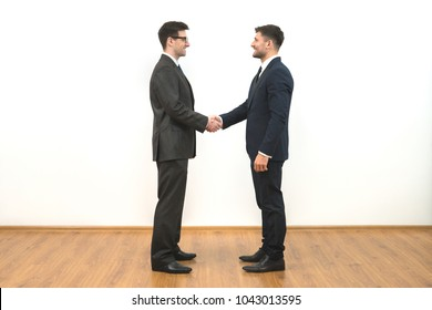 The two businessmen handshake on the white wall background