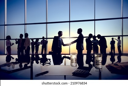 Two Businessmen Handshaking Together with Their Colleagues
