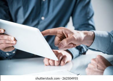 Two businessmen having a discussion over information displayed on a tablet computer, close up of their hands pointing to the screen in a teamwork concept