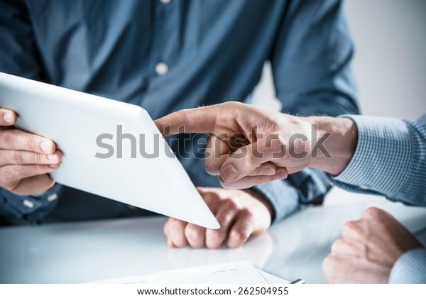 Zwei Geschäftsmänner diskutieren über Informationen, die auf einem Tablet-Computer angezeigt werden, Nahaufnahme ihrer Hände, die in einem Teamwork-Konzept auf den Bildschirm zeigen