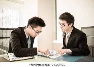 Two Businessmen Having Informal Meeting In Modern Office.Asian