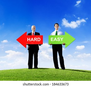 Two Businessmen Holding Arrows for Hard and Easy