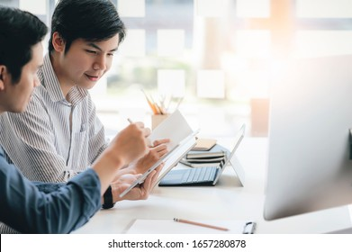 Two businessmen holding tablet and paperwork discussing together while sitting at office desk in modern office.