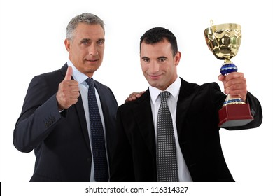 Two businessmen holding trophy