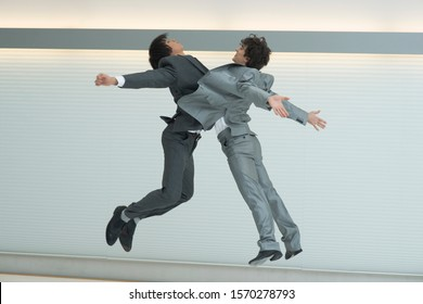 Two businessmen jumping in the air, bodies clashing