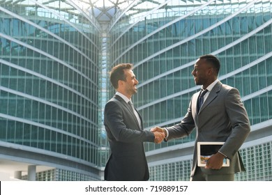 Two businessmen, just concluded a job contract, are shaking hands with their success in the economic and financial sphere. Concept of: team, business, success.
