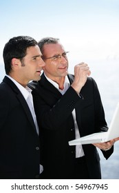 Two businessmen with a laptop computer looking away