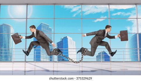 Two businessmen linked chain running