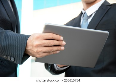 Two businessmen looking at tablet pc - business discussion concept
