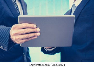 Two businessmen looking at tablet pc, business discussion concept - vintage tone
