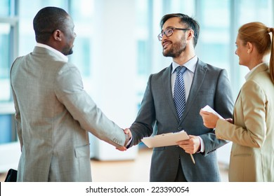 Two businessmen making agreement, their female colleague standing near by