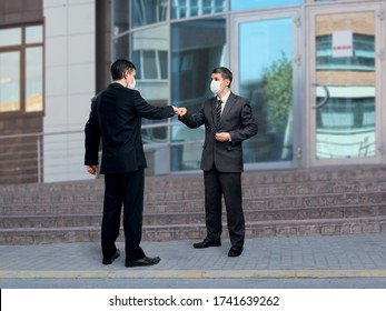 Two businessmen in medical face masks stand on the street near the steps at the entrance to the building. They practice greeting bump fists, abandoning the traditional handshake