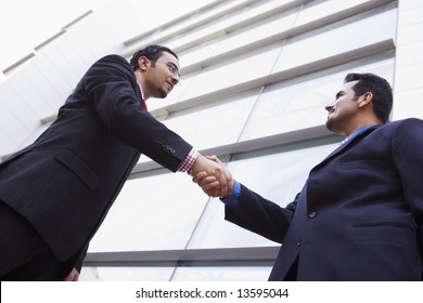 Two businessmen meeting outside modern office building