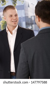 Two businessmen meeting outside of office building, smiling.