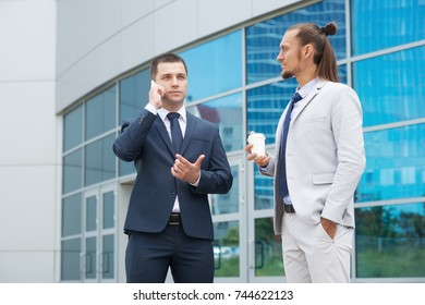 Two businessmen are negotiating on the background of the business center