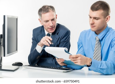 Two businessmen old and young during a meeting checking documents and discussing problems