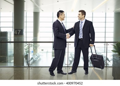 two businessmen, one asian and one caucasian, shaking hands and smiling at modern airport.