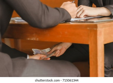 Two businessmen are paying money under the office desk for corruption.