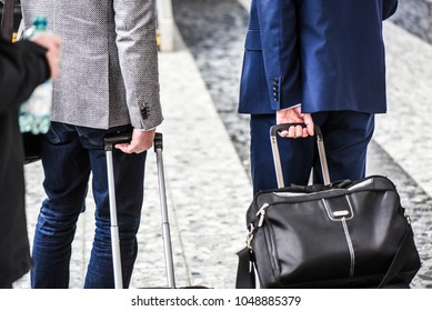 Two businessmen in perfect suit pull suitcase at airport. Man holding suitcase close up.