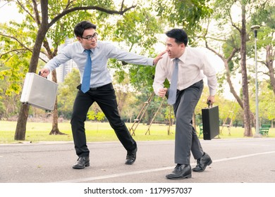 Two businessmen are race running in the park.