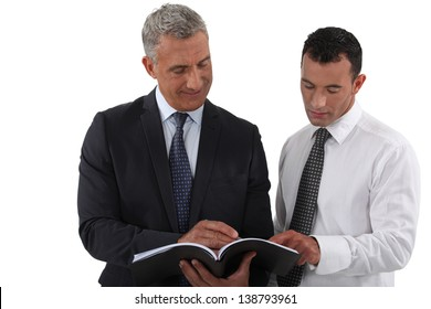 Two businessmen reading document
