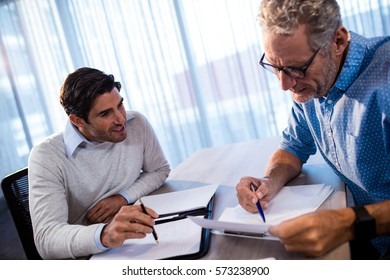 Two businessmen reading a document and interacting in the office