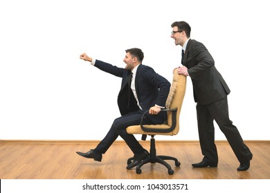 The two businessmen ride on the chair on the white wall background