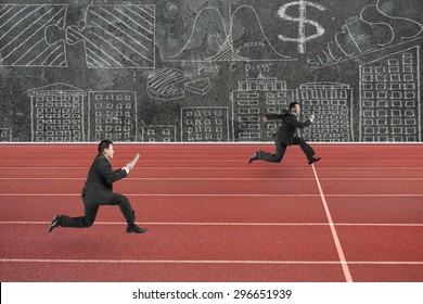 Two businessmen running on red track, with business concepts doodles wall background.
