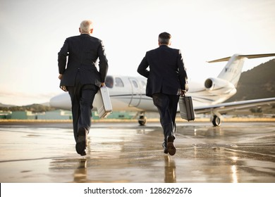 Two businessmen running towards a private jet