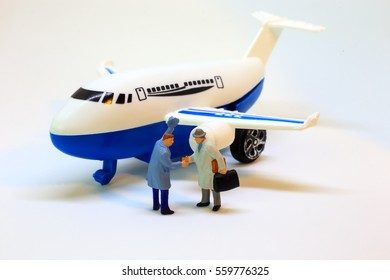 Two businessmen are shacking hand at the airport after arrival from journey. Tourism concept from figurine model.