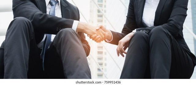 Two businessmen shake hands after agreeing to a joint business deal.