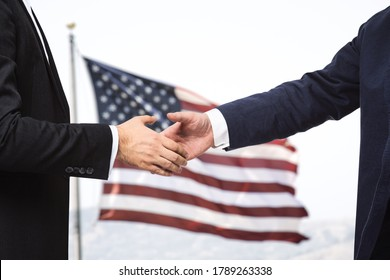 Two businessmen shake hands on the background of USA flag, partnership concept, close up