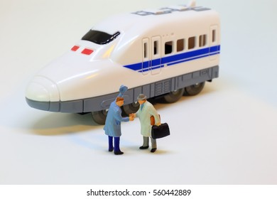 Two businessmen are shaking hand at train station after arrival from journey. Tourism concept from figurine.