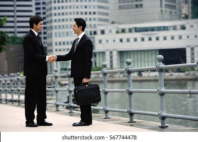 Two businessmen shaking hands, buildings in the background