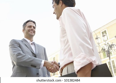 Two businessmen shaking hands in the city, smiling.