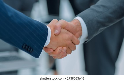 Two businessmen shaking hands with colleagues on background.