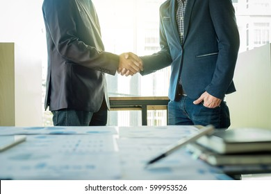 Two businessmen shaking hands during a meeting in the office, success, dealing, greeting & business partner.