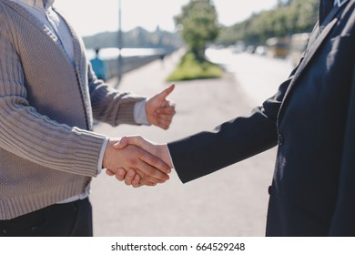 Two businessmen shaking hands during a successful deal in the street