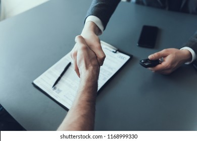 Two Businessmen Shaking Hands Finishing Up Meeting. Adult Man Signing Contract in Showroom Office. Close-up of Car Buying Deal. Acquisition Concept. Business Partnership Concept.