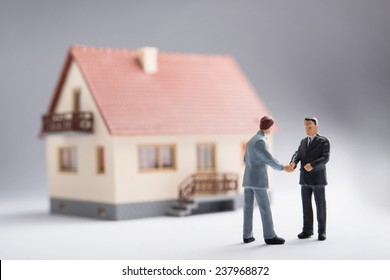 Two businessmen shaking hands in front of a house