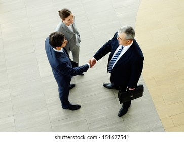 Two businessmen shaking hands indicating successfully made deal