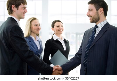 Two businessmen shaking hands in a modern office environment