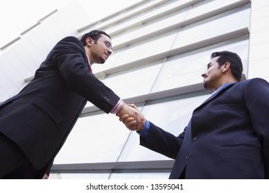 Two businessmen shaking hands outside modern office building