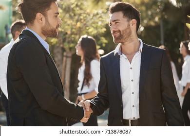 Two businessmen shaking hands outside