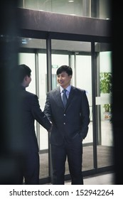 Two businessmen shaking hands, seen through glass wall